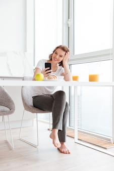Lovely beautiful woman holding her head while reading message on smartphone at the kitchen