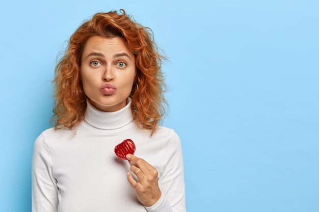 Lovely beautiful woman with natural red hair, smooth skin, green eyes, keeps lips folded, holds small red heart, expresses love and affection, wears white turtleneck, looks straightly