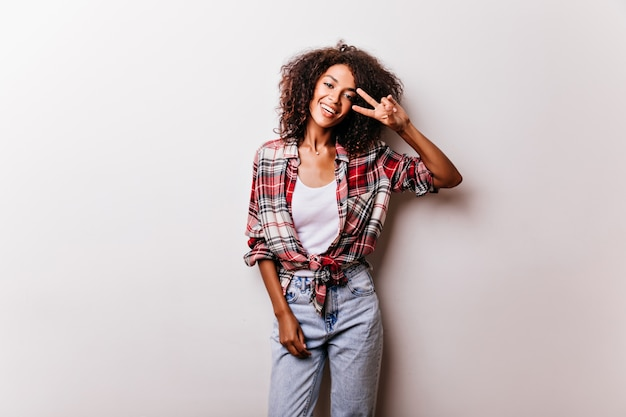 Lovely black girl in vintage denim pants posing with peace sign. enthusiastic female model in checkered shirt isolated on white.