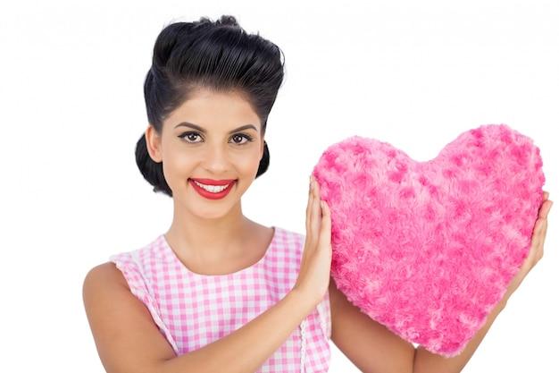 핑크 하트 모양의 베개를 들고 사랑스러운 검은 머리 모델