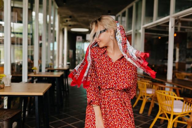 Bella donna bionda felice che cammina fuori indossando abito rosso brillante e scialle in testa