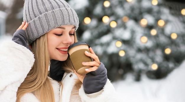 冬の公園でコーヒーを楽しんでいる素敵な金髪の女性。空きスペース