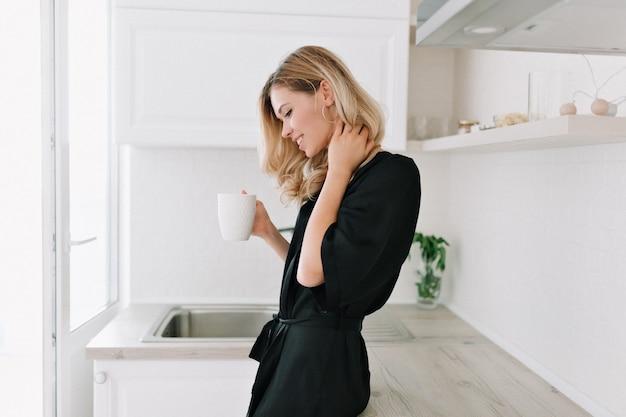 한 잔의 커피와 미소와 함께 흰색 세련 된 아파트에서 창 앞에 서있는 사랑스러운 금발 여자. 소녀는 커튼을 열고 일출을 만나고 있습니다. 매력적인 아가씨와 함께하는 아침