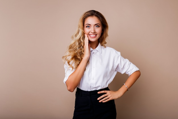 Lovely blond woman with perfect smile in white blouse posing over beige wall. stylish workwear outfit.