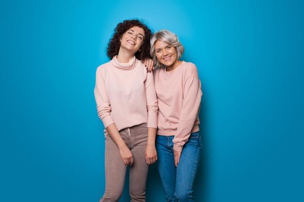 Милые сестры блондинки и брюнетки позируют на синей стене в студии в одних и тех же свитерах и джинсах, весело улыбаясь в камеру