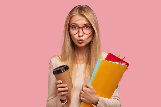 Bella studentessa di college bionda in posa contro il muro rosa
