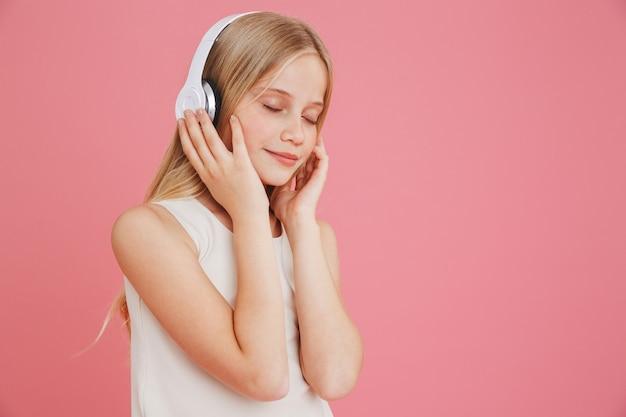 ピンクの背景で隔離、目を閉じて音楽を聴き、頭でワイヤレスヘッドフォンに触れるカジュアルな服を着た素敵なブロンドの女の子8-10
