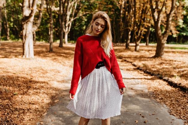 秋の公園でポーズをとる素敵なブロンドの女の子。素敵な赤いセーターと美しい白いドレスを着ています。