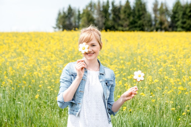 Lovely blonde girl,rapeseed flowering field. yellow flowers, in hands chamomiles candy on stick,sweet flower, hides eye, brought it to his face. summer day in village. freedom, air is the wind