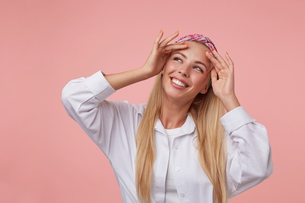 Lovely blonde lady with raised hands to her forehead, wearing casual clothes, looking happily aside, isolated