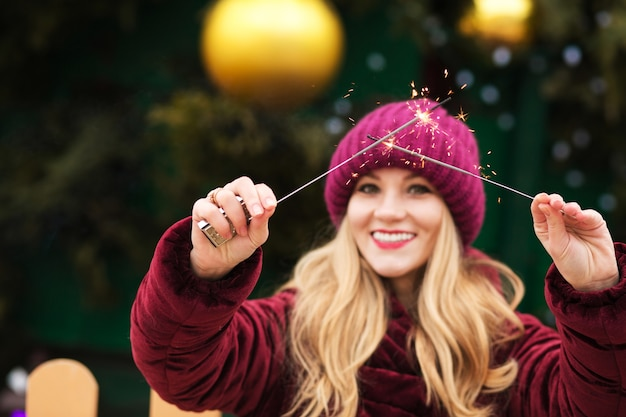 キエフのメインのクリスマスツリーで輝くベンガルライトを保持している素敵な金髪のモデル。ぼかし効果