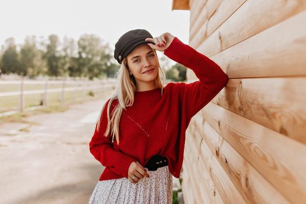 멋진 금발 멋지게 야외 목조 주택 근처 웃 고. 공원에서 유행 계절 옷을 입고 포즈를 취하는 매력적인 소녀.