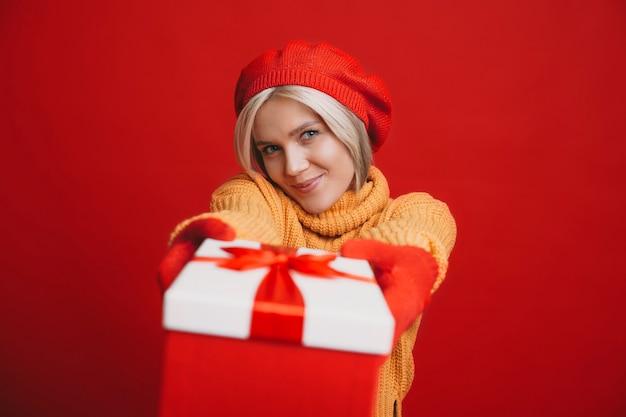 Прекрасная блондинка с короткими волосами, глядя на камеру, улыбается и дает вам красную подарочную коробку, изолированную на красной стене студии.