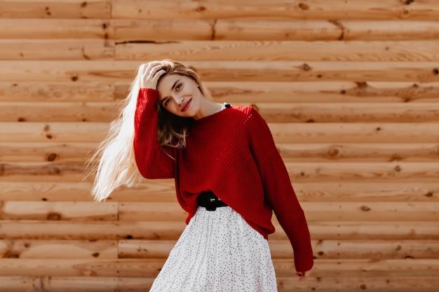 Bella bionda in maglione rosso alla moda che si diverte molto fuori. giovane donna allegra che posa felicemente sulla parete di legno.