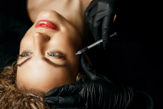 彼女の頬骨にフィラー注射をしている素敵なブロンドの女性。美容の概念。上面図