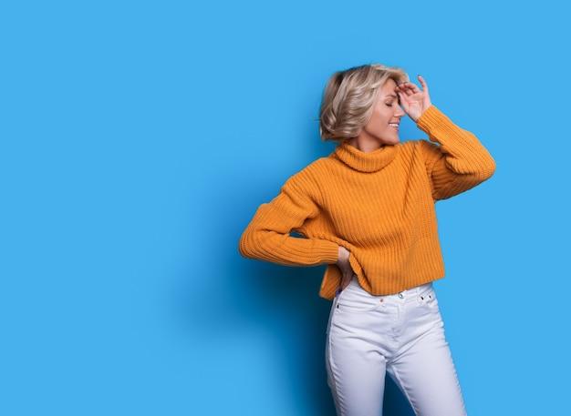 ニットのセーターを着た素敵な金髪の女性は、空きスペースのある青い壁に彼女の顔に手でポーズをとっています