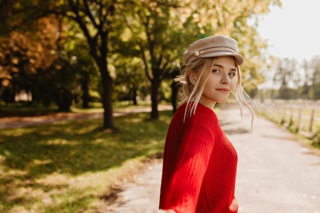 Bella donna bionda che osserva affascinante seguendo una persona nel parco d'autunno.