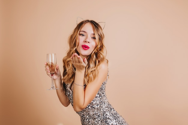 Lovely blonde woman in sparkle attire sending air kiss standing on light wall with wineglass