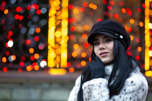 通りでポーズをとって黒い帽子をかぶっている素敵なブロンドの女性
