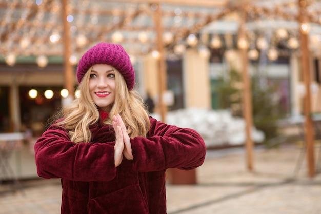 キエフの通りで花輪の背景にポーズをとって、赤いニット帽と冬のコートを着ている素敵な金髪の女性