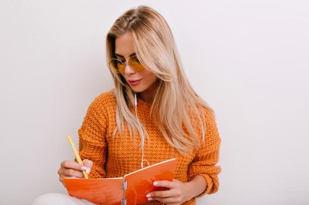 Bella donna bionda con manicure elegante scrivendo qualcosa in taccuino colorato con un sorriso delicato