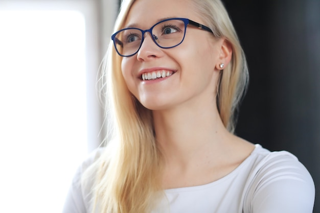 Lovely blonde woman with eyeglasses posing in white shirt