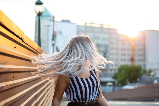 Прекрасная блондинка с развевающимися волосами, позирует в вечернем свете. место для текста