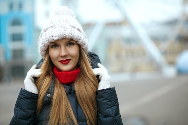 街歩きを楽しんで、ニット帽をかぶった赤い口紅の素敵なブロンドの女性。テキスト用のスペース