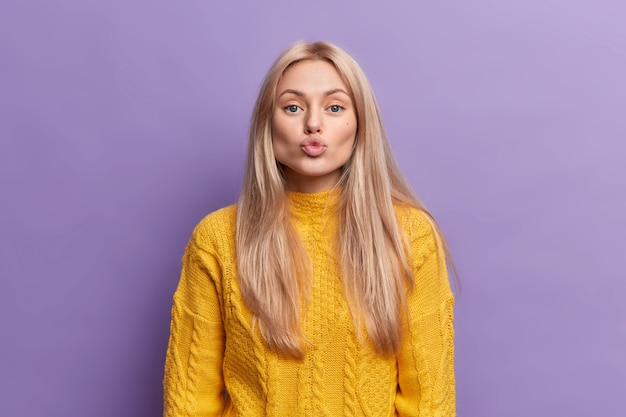Lovely blonde young woman folded lips blow kiss has romantic face expression expresses sympathy confesses in love to boyfriend wears casual yellow sweater