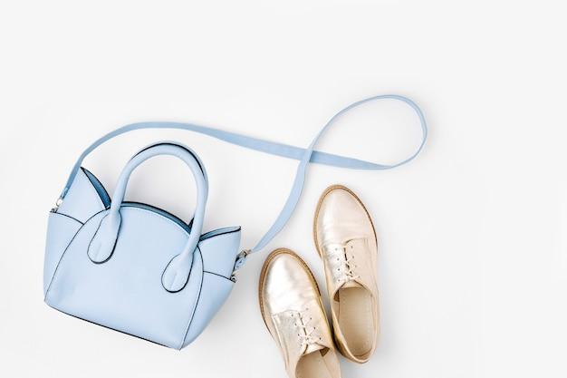 素敵な青いレディースバッグとスタイリッシュな金色の靴。フラットレイ、上面図。春のファッションコンセプト