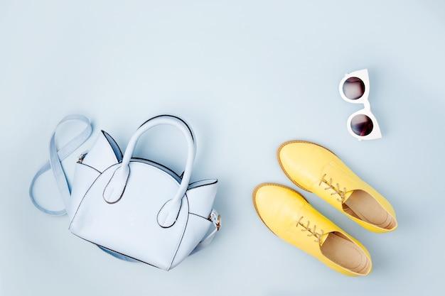 素敵な青いレディースバッグ、サングラス、スタイリッシュな黄色い靴。春のファッションコンセプト