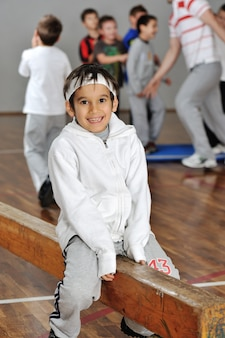 Lovely boy in front of his friends and trainer in gym hall