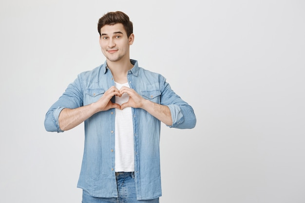Lovely boyfriend show heart gesture and smiling