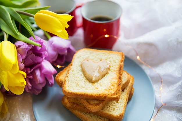 Lovely breakfast in bed. black coffee, bright flowers, toast with peanut butter.