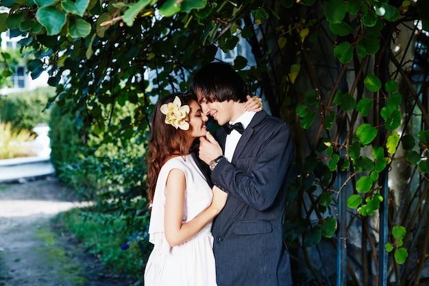公園の背景、結婚式の写真、美しいカップル、結婚式の日、愛で互いに近くに立っている素敵な花嫁と花婿。