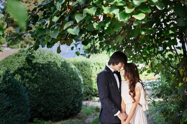 公園の背景、結婚式の写真、美しいカップル、結婚式の日に互いに近くに立っている素敵な花嫁と花婿。