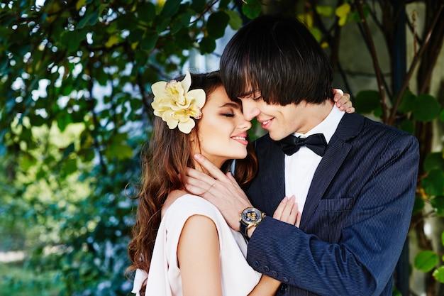 公園の背景、結婚式の写真、愛、美しいカップル、結婚式の日に近くに立っている素敵な花嫁と花婿。