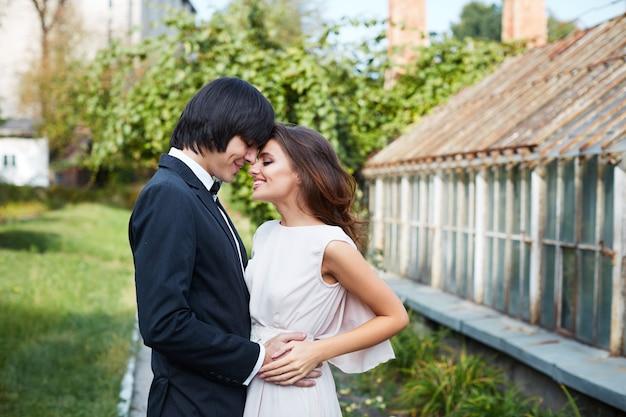 Прекрасная невеста и жених, стоя близко друг к другу в парке, свадебное фото, красивая пара, день свадьбы, портрет крупным планом.