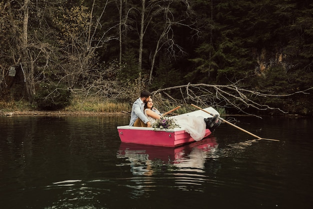 Прекрасная невеста и жених сидят вместе в розовой лодке на озере.