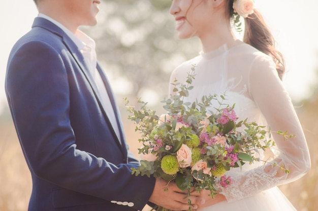 Lovely bride and groom hold a bouquet of flowers and smile together. love concept