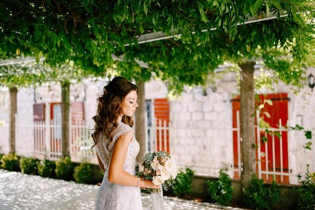 緑の庭でバラの美しいウェディングブーケと豪華なドレスを着た素敵な花嫁が立っています