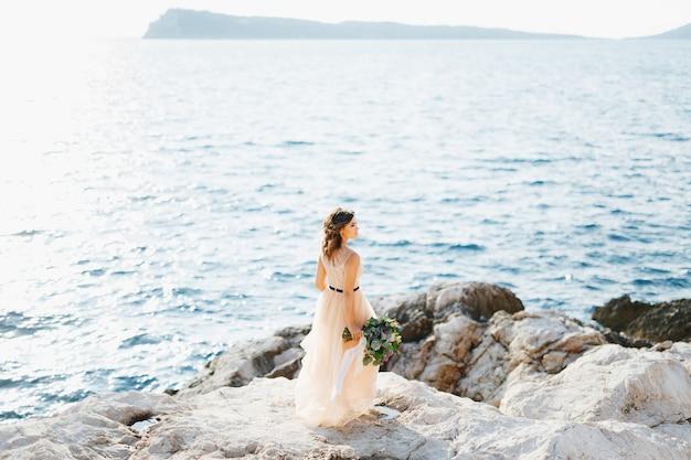 파스텔 웨딩 드레스의 사랑스러운 신부는 꽃의 꽃다발과 함께 바다 위의 바위에 선다