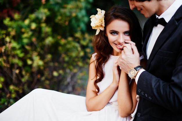 긴 곱슬 머리와 신랑 녹색 잎 배경, 웨딩 사진, 아름 다운 커플에서 서로 가까이 서있는 사랑스러운 신부.