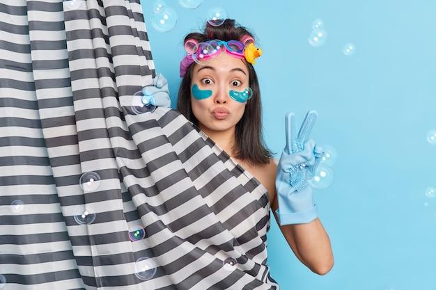 La bella donna asiatica bruna applica cerotti al collagene mentre fa la doccia fa un gesto di pace subisce procedure di bellezza si nasconde dietro la tenda della doccia posa contro le bolle di sapone della parete blu intorno