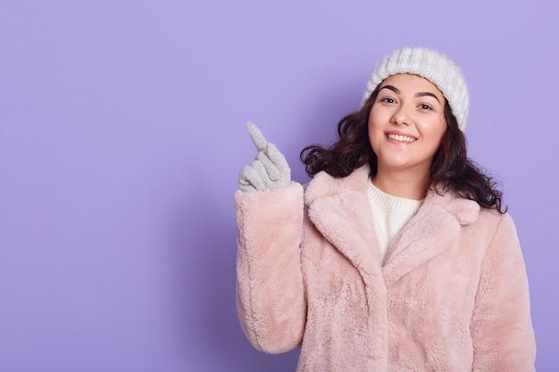 幸せな表情で素敵なブルネットの女性、ピンクの毛皮のコート、キャップ、ミトンを着ています