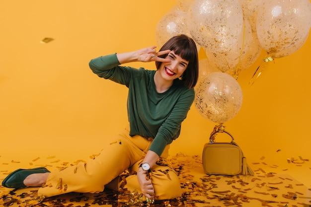 ピースサインでポーズをとる素敵なブルネットの少女。誕生日パーティーの準備をしている嬉しい若い女性の肖像画。