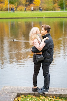 Lovely brunette guy and pretty girl blonde on date. loving teenagers are happy, smiling, kissing.