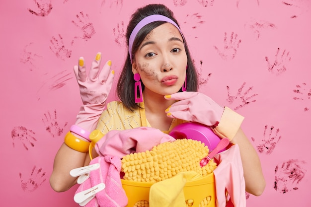 Lovely brunette housewife looks attentively at camera keeps lips rounded wears rubber gloves busy doing laundry at home finished all important tasks works according special cleaning schedule