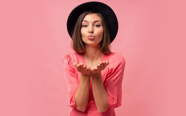 사랑스러운 갈색 머리 짧은 머리 여자 센 키스와 분홍색 벽에 포즈.