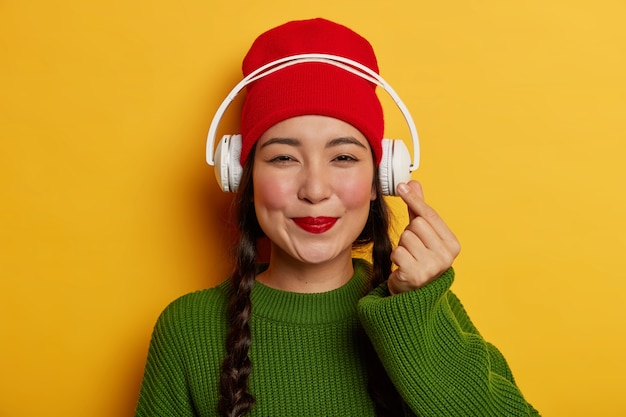 赤い帽子と緑のジャンパーで素敵なブルネットの女性は、オーディオトラックを聴きます